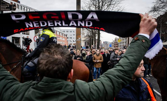 Archiefbeeld: Een demonstrant van Pegida toont zijn sjaal tijdens een demonstratie