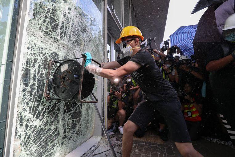 Een demonstrant gooit een raam in van het parlementsgebouw in Hongkong. Beeld EPA