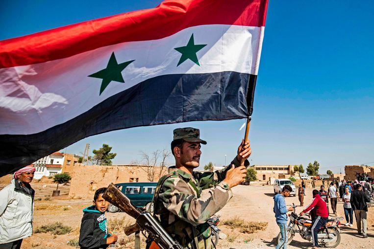 Een Syrische soldaat loopt met de nationale vlag over straat in het stadje Tall Tamer.  Beeld AFP