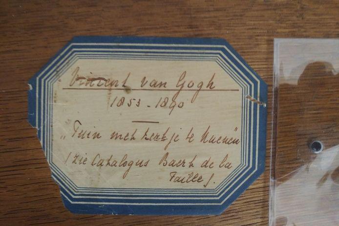 De tweede foto is van een etiket aan de achterkant van het schilderij.