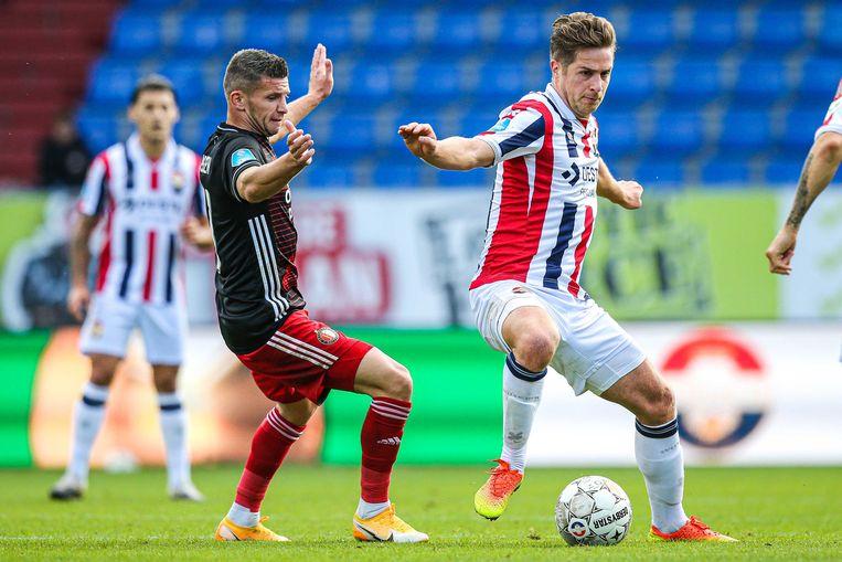 Willem II-aanvoerder Jordens Peters in duel met Feyenoorder Bryan Linssen, zondag 4 oktober. In een leeg stadion in Tilburg werd het 1-4.  Beeld ANP