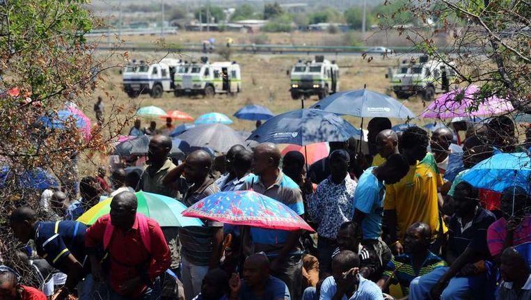 Mijnwerkers onderweg naar een rouwbijeenkomst voor door de politie gedode collega's. Beeld afp