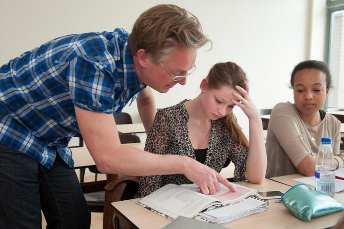Eindexamenleerlingen op een middelbare school. Docent legt een meisje aan haar tafeltje iets uit.
