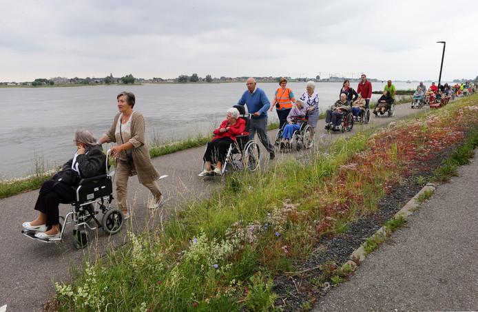 De stoet met bewoners van De Lange Wei trekt in het frisse weer langs de Merwede.