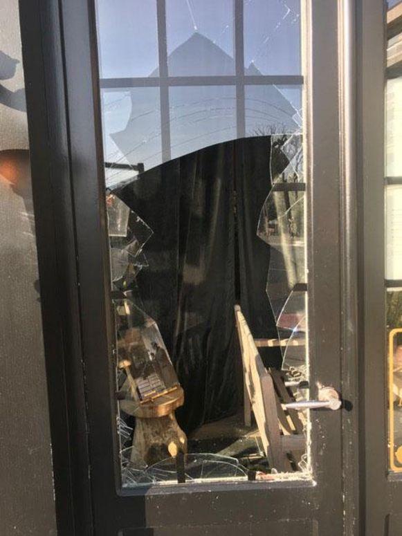 De vernielde glazen deur.