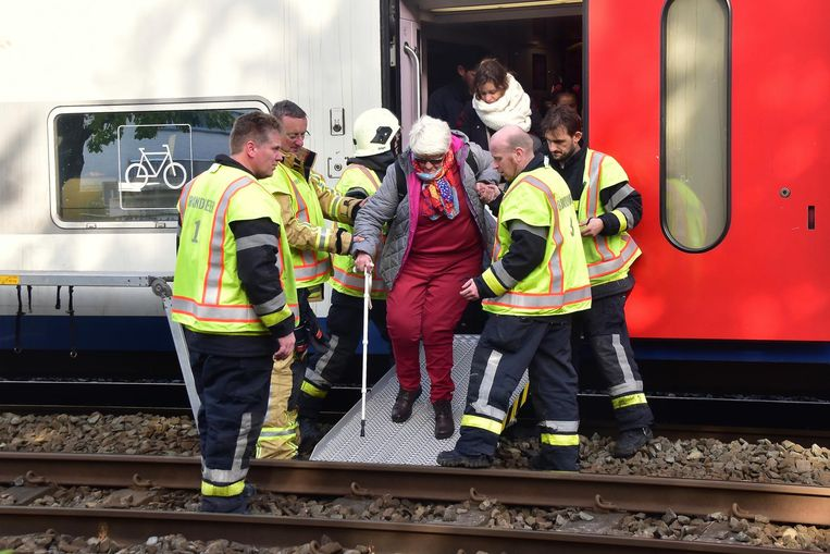 Een gestrande treinreiziger wordt uit de trein geholpen.