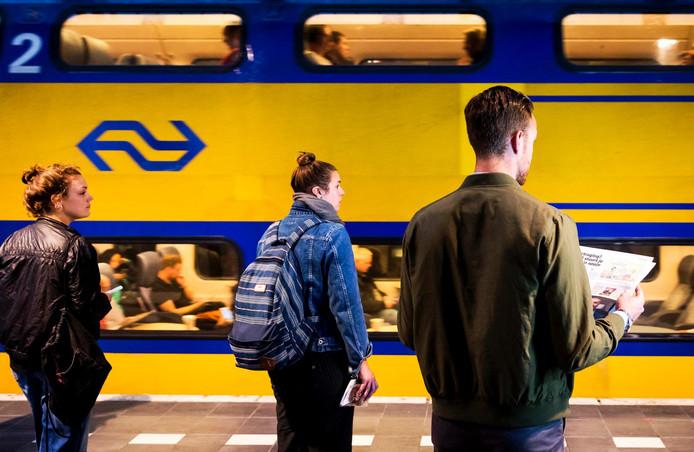 Treinreizigers wachten op het station.