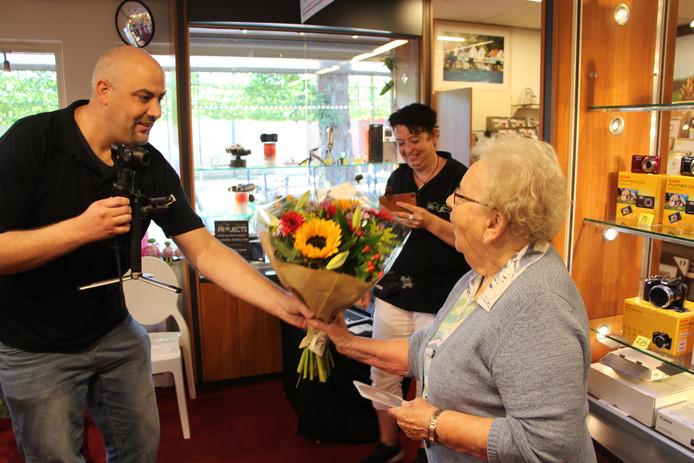 Rudy Exterkate overhandigt Dinie Schaperclaus in Eibergen behalve een dvd ook een boeket bloemen ter gelegenheid van de promotie van de N18-dronereportages-compilatie.