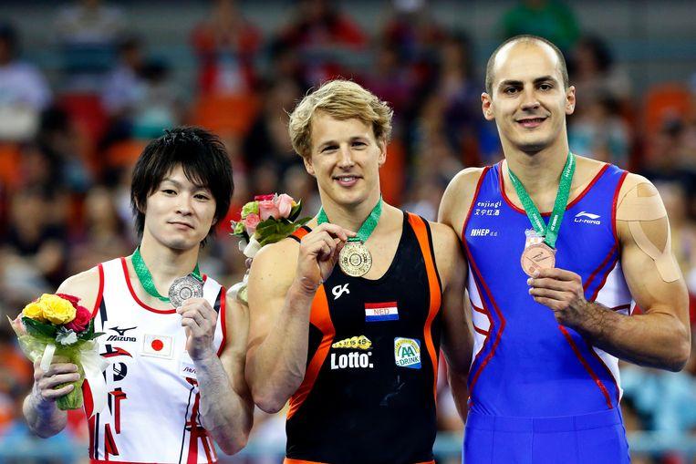 Epke Zonderland (midden) met zijn gouden medaille tijdens de WK turnen in Nanning. Beeld epa