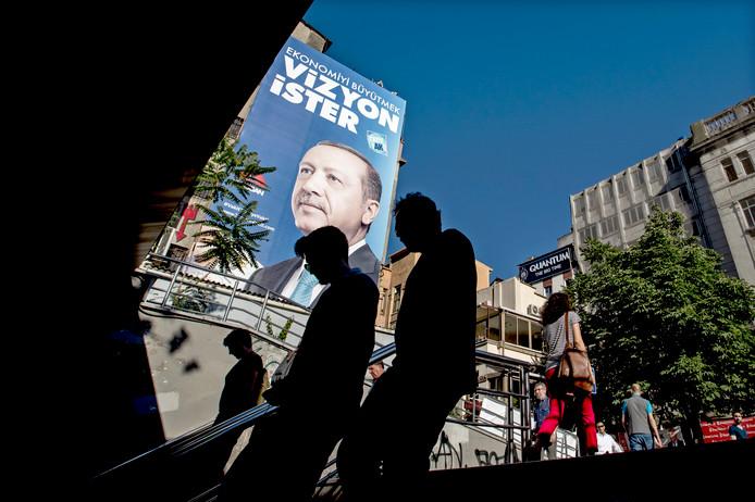 Publiek loopt in Istanboel langs een verkiezingsposter van Recep Tayyip Erdogan.