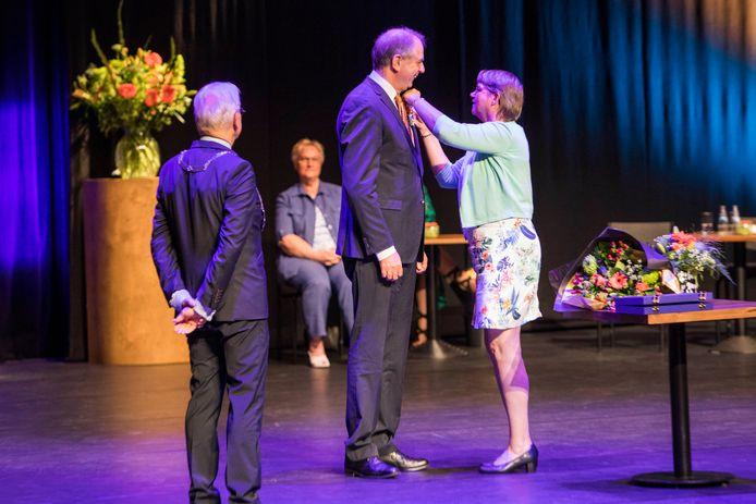 """Zoetermeerder Wim Kokx krijgt het lintje opgespeld door zijn vrouw. ,,Het opspelden is een gedoe door de dikke stof van de kleding, maar mijn vrouw is zo sluw om het speldje door het knoopsgat te doen."""""""