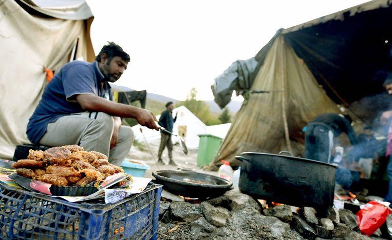 Migranten uit Afrika en Azië voor hun tentjes in het vluchtelingenkamp Vucjak.  Beeld AFP