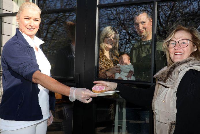 Kraamverzorgende Connie van den Broeke (links) serveert buiten beschuit met muisjes aan oma Sylvia, kersverse moeder en vader Kelly en Robin met baby Liz kijken van binnenuit toe.