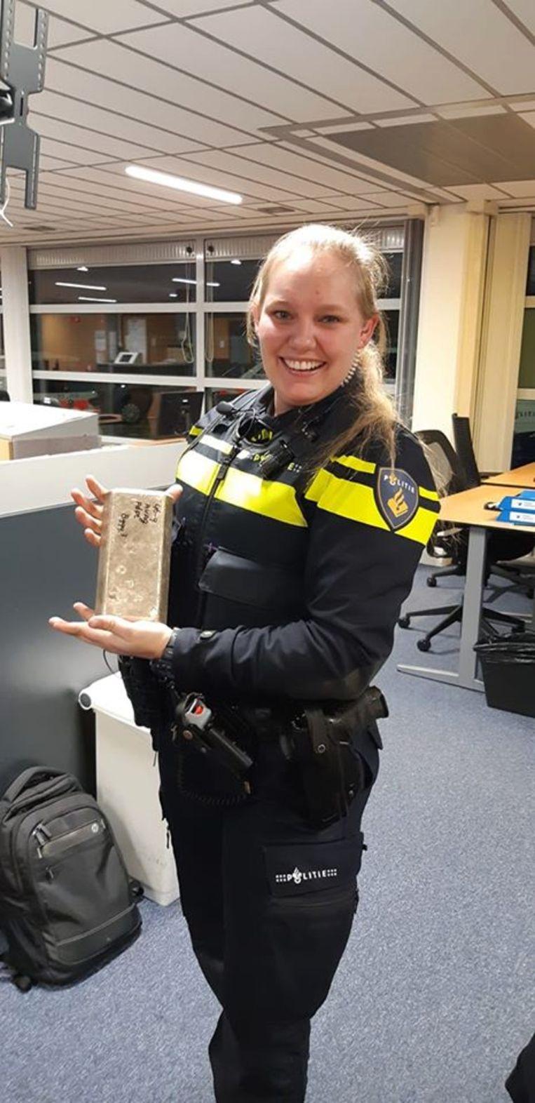 Een agent van de politie Utrecht pronkt met de gevonden goudstaaf