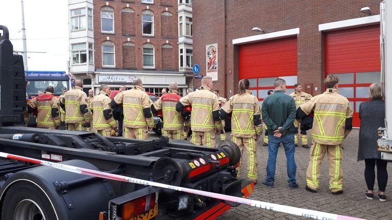 Brandweermannen vormen een erehaag voor de kazerne in de Marnixstraat. Beeld Hanneloes Pen