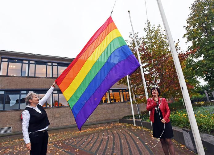 Oostburg;  Regenboogvlag wordt gehesen door burgemeester Marga Vermue van Sluis, geassisteerd door ambtenaar Monique.