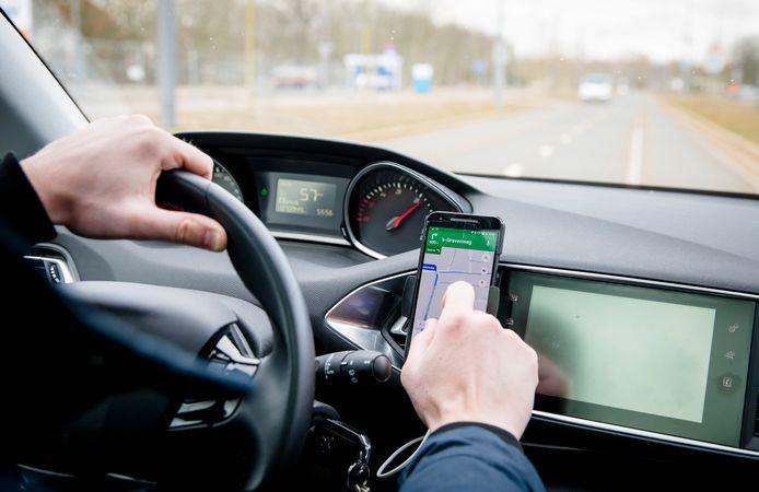 Een automobilist stelt de navigatie van zijn telefoon in tijdens het rijden.