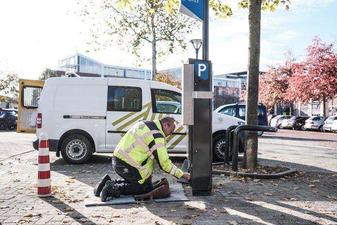 Een elektromonteur koppelt de zuil voor stadsparkeren aan de nieuwe parkeerautomaat op het parkeerterrein aan de Kampsingel in Zevenaar.