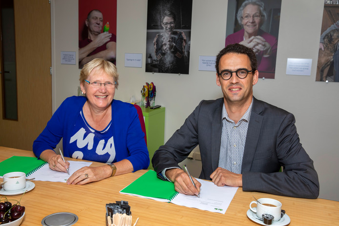 Truus Sweringa, directeur bestuurder OFW, en Arjan Berends, algemeen directeur Salverda Bouw, zetten hun handtekening onder het contract voor groot onderhoud van 104 huurwoningen in Dronten.