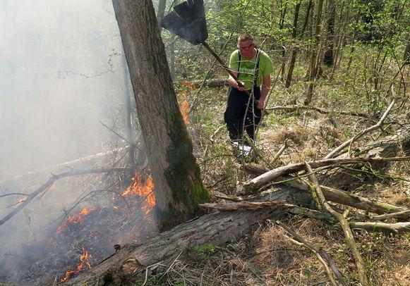 Een brandweerman slaat met een bezem op de vlammen.