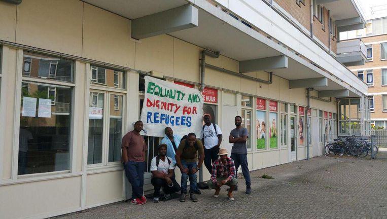 Een aantal vluchtelingen voor hun nieuwe onderkomen Beeld Wij Zijn Hier
