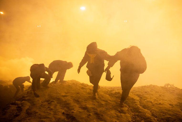 Een groep migranten bij de Mexicaanse grens bij Tijuana vlucht op Nieuwjaarsdag voor traangas, dat door de Amerikaanse grenspolitie is afgevuurd.  Beeld Getty Images