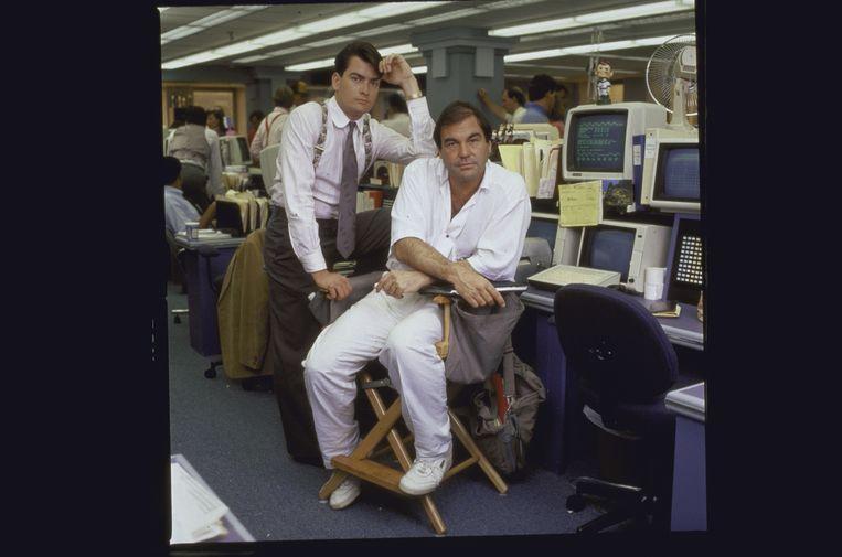Oliver Stone (rechts) met Charlie Sheen op de set van Wall Street (1987). Beeld Getty