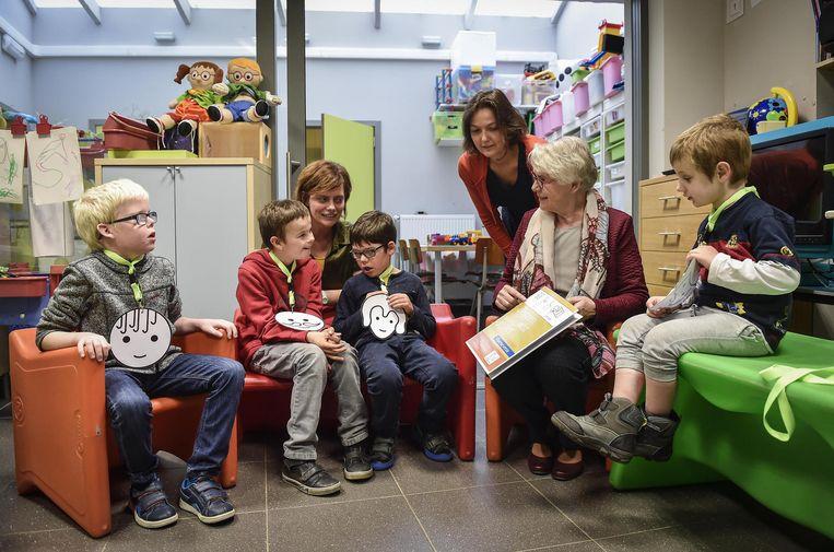 Kinderen en leerkrachten bekijken het boek samen met Trijntje de Wit.