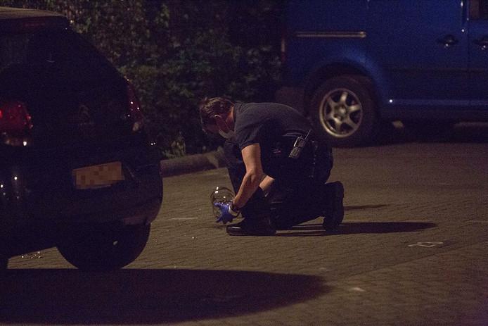 Een agent is bezig met onderzoek op de plek waar eerder die avond geprobeerd is een auto in brand te steken.