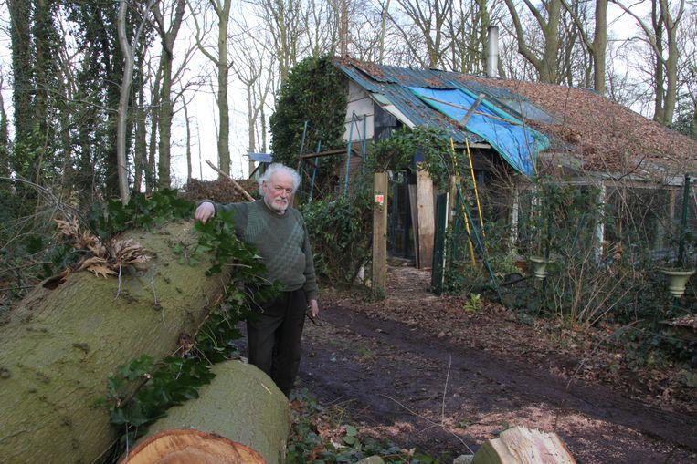 Bewoner Tillo Maertens bij de restanten van de omgevallen boom die op het dak van zijn woning terecht kwam.