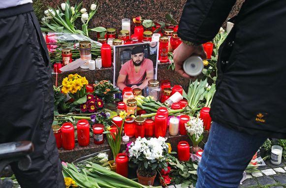 Mensen leggen bloemen neer en steken kaarsen aan bij een foto van Ferhat Unvar, een van de slachtoffers van de aanslag.