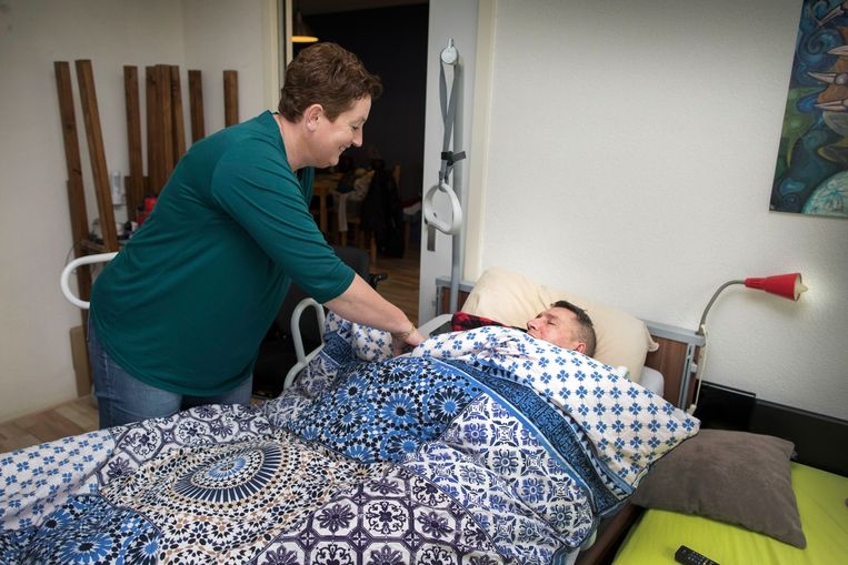 Wijkverpleegkundige Annemarie Stout verzorgt cliënt Paul. Beeld Werry Crone