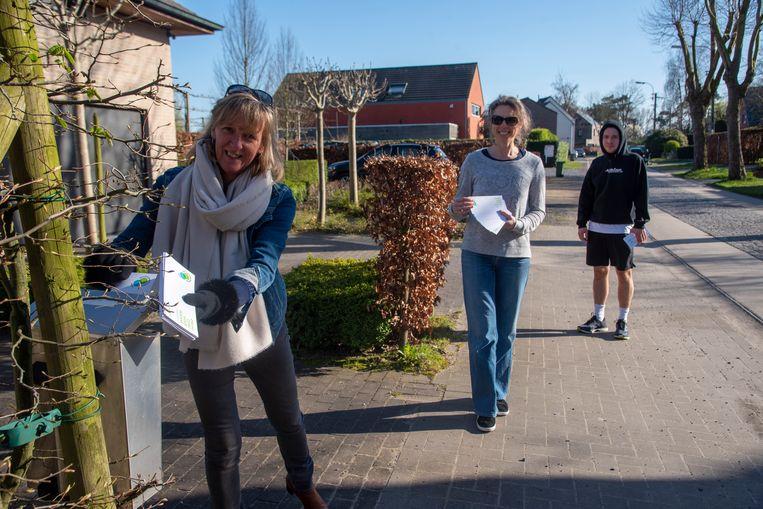 Burgemeester Elsie Sierens en haar buren posten burenkaartjes in hun straat in Destelbergen.