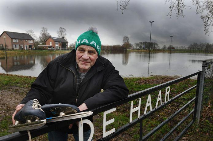 Ries Smits met zijn schaatsen en ijsmuts bij de watervlakte die eigenlijk ijsbaan zou moeten zijn in Enspijk.