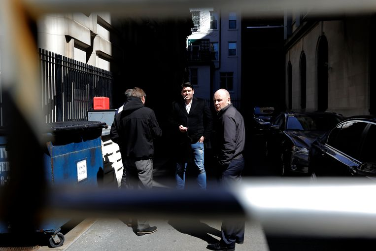Medewerkers van de Russische ambassade in New York roken in een zijstraat. Beeld EPA