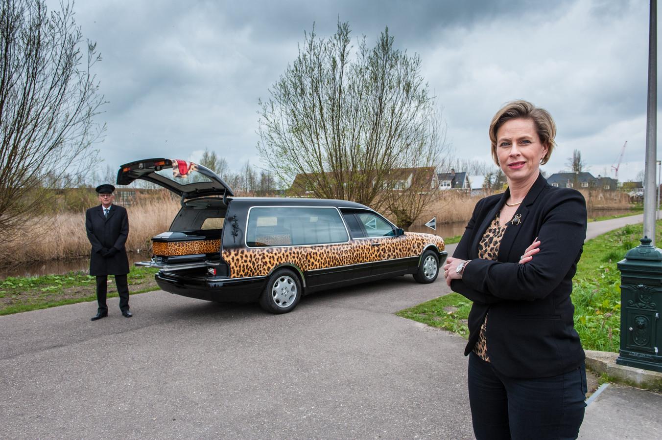 Brigitte Straver en chauffeur Wim van de Coevering bij de bijzondere uitvaartauto.