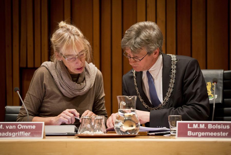 Burgemeester Bolsius en raadsgriffier Van Omme tijdens een raadsvergadering