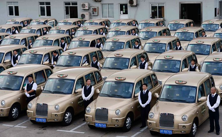 Chauffeurs staan bij de taxi's van Geely, die gebaseerd zijn op de 'London cab'. De Chinese taxi's zijn niet zwart maar 'champagne-goud'.  Beeld REUTERS