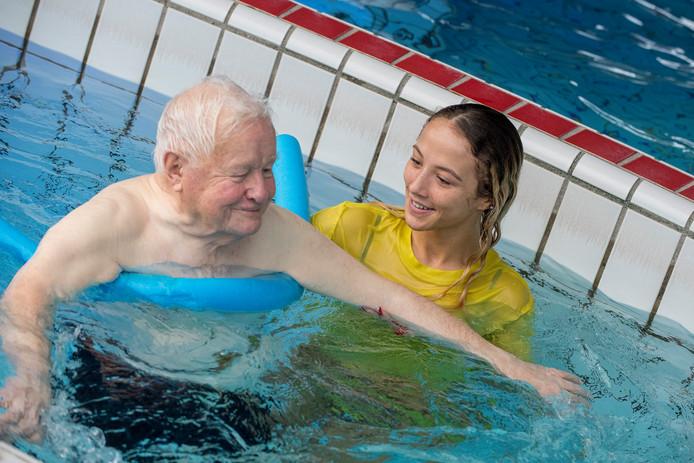 Een studente van het ROC Rivor zwemt met een bewoner van zorgcentra De Betuwe.
