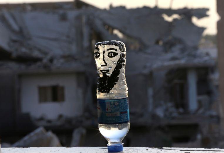 Waterflesje met portret van een IS-strijder, gevonden in de Syrische stad Raqqa. Beeld AP