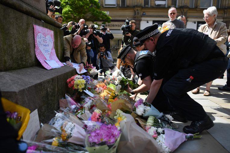 Mensen leggen bloemen voor de slachtoffers van de aanslag bij Manchester Arena.  Beeld AFP