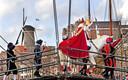 Sinterklaas op zijn paard met op de achtergrond een van de molens van Schiedam.