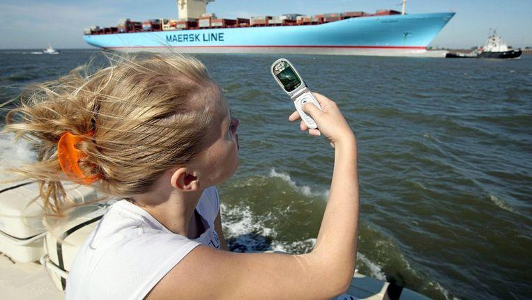 Een vrouw neemt een foto van een containerschip Beeld epa
