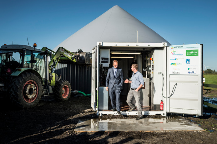 Een opslagtank en een container, meer is er niet nodig voor mestvergisting. Minister Kamp (links) ziet er veel in.