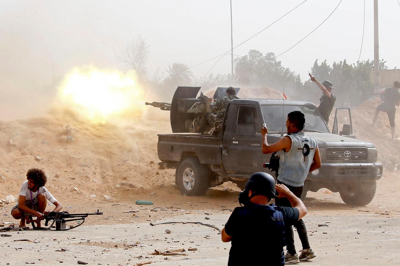 Een soldaat trouw aan het Libische internationaal erkende Government of National Accord (GNA) schiet met een machinegeweer terwijl een persfotograaf foto's maakt van de scene, mei 2019. Beeld AFP