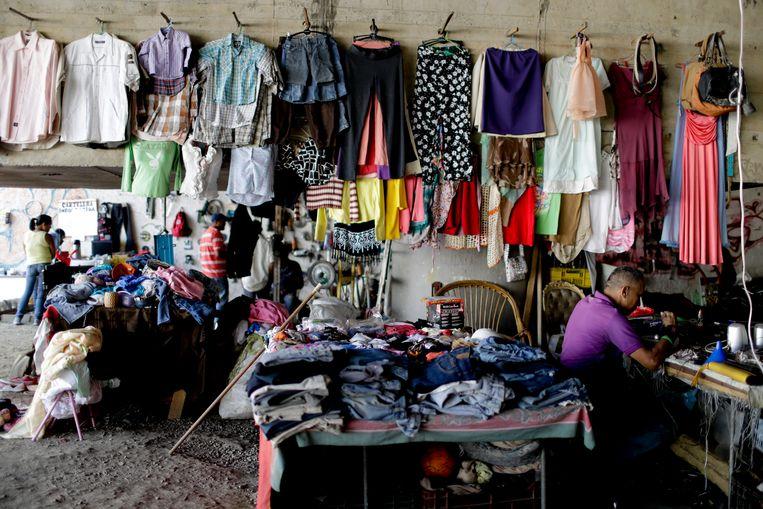 Een geïmproviseerde winkel voor tweedehands kleding in de Venezolaanse hoofdstad Caracas. Het IMF waarschuwt voor groeiende armoede na de coronapandemie in landen die sterk afhankelijk zijn van grondstoffen en buitenlandse familieleden die geld sturen.  Beeld AP