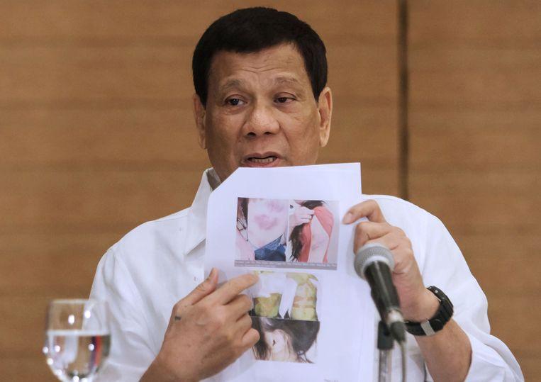 De Filipijnse president Rodrigo Duterte toont foto's van de stoffelijke resten van een landgenote die dood werd aangetroffen in Koeweit.