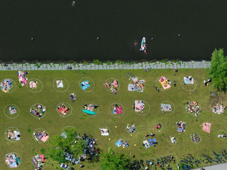 Park Somerlust in Amsterdam, in het park zijn cirkels aangebracht ter verduidelijking van de 1,5 meter afstand die de bezoekers moeten aanhouden. Beeld Marco van Middelkoop