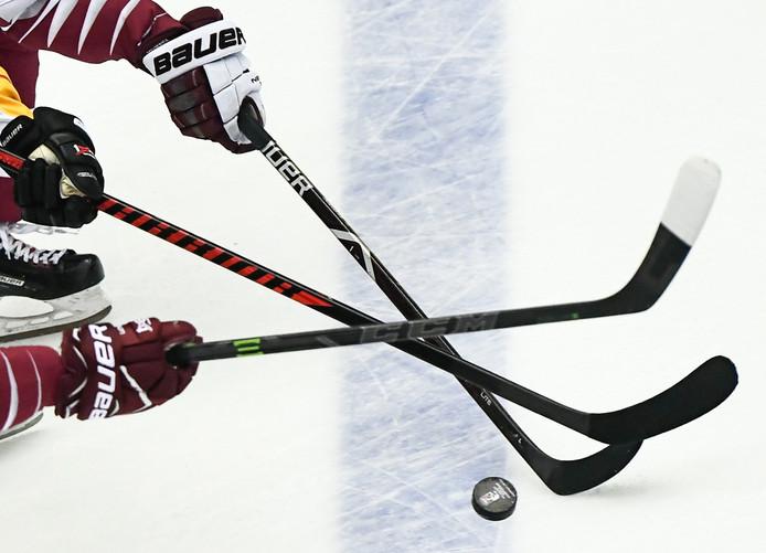 IJshockeyers van Duitsland en Letland reiken naar de puck tijdens het WK in het Deense Herning.