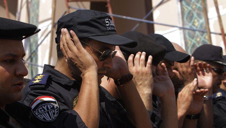 Politieagenten bidden tijdens een begrafenis van een van hun collega's. Beeld ap